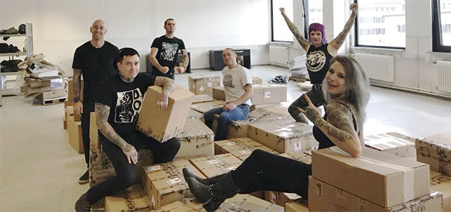 Staff sitting on boxes at the Deidre Berlin Warehouse