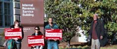 Three people with signs grouped togther and one man standing to the side