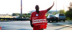 Man holding sign while raising one hand up