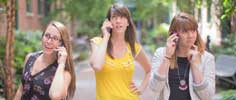 Three young women talking on cell phones