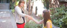 Two young women shaking hands
