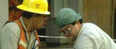 Two construction men left man is wearing a yellow hardhat the right man  has a green beanie and is wearing glasses