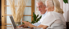 Older man and woman sitting togther in front of laptop computer